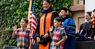 Ireri E. Chávez-Bárcenas' sons proudly share the stage with her as she receives her hood from Wendy Heller, our Chair and the